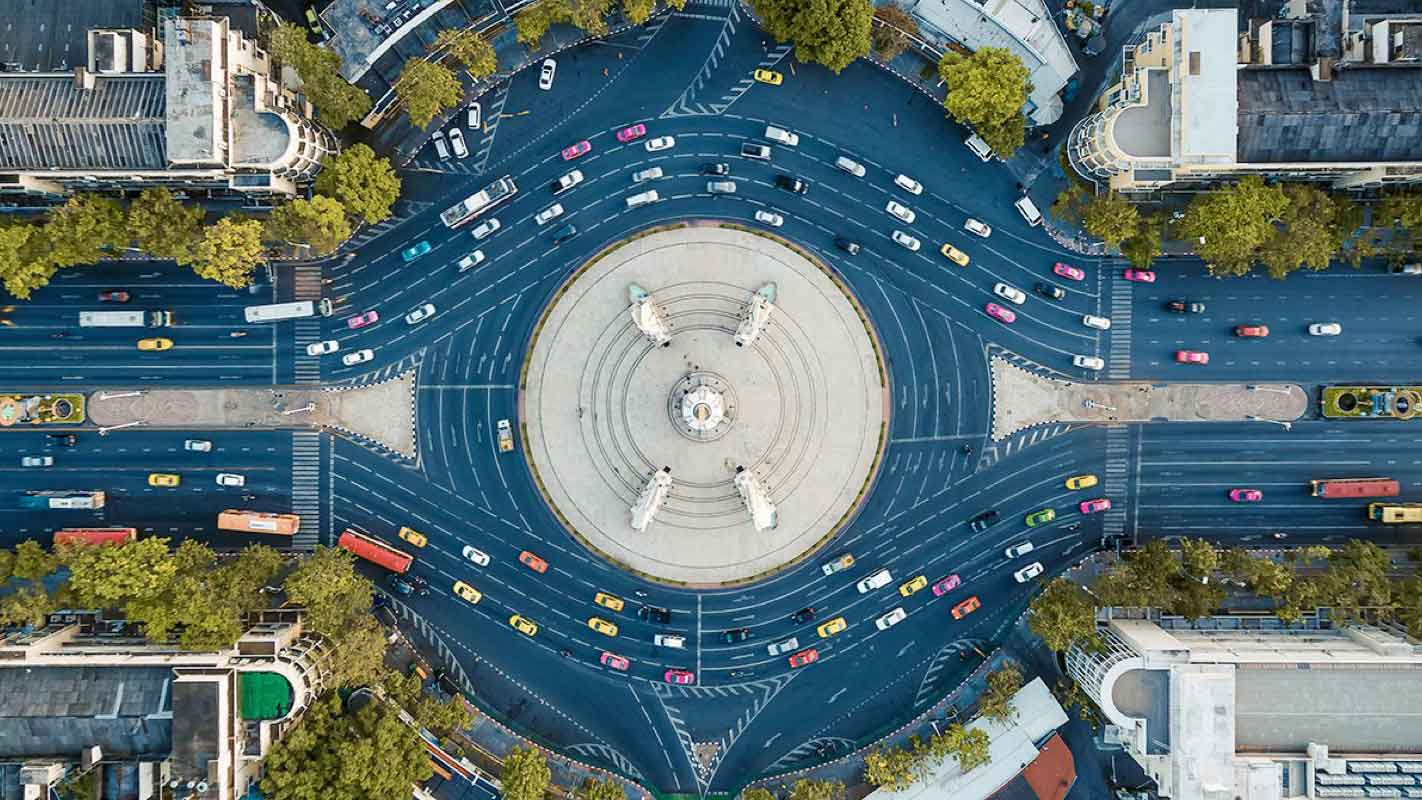 Overhead view of a four-lane traffic circle with traffic