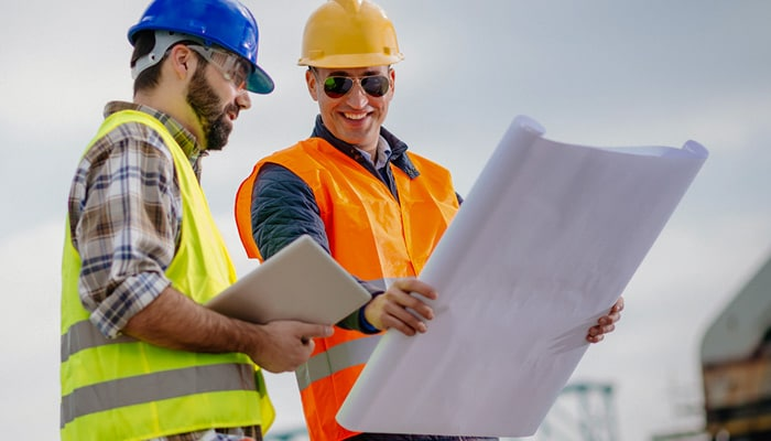 Two man wearing hard hats looking at blueprint