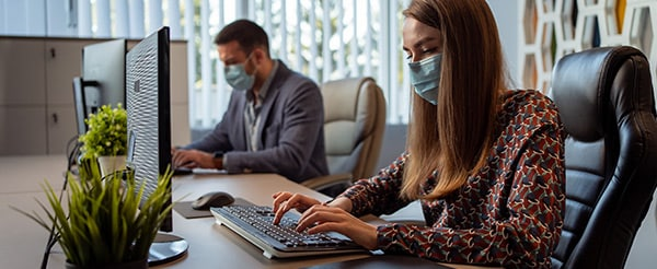Two office workers wear protective masks, while sharing a desk and working on their PCs