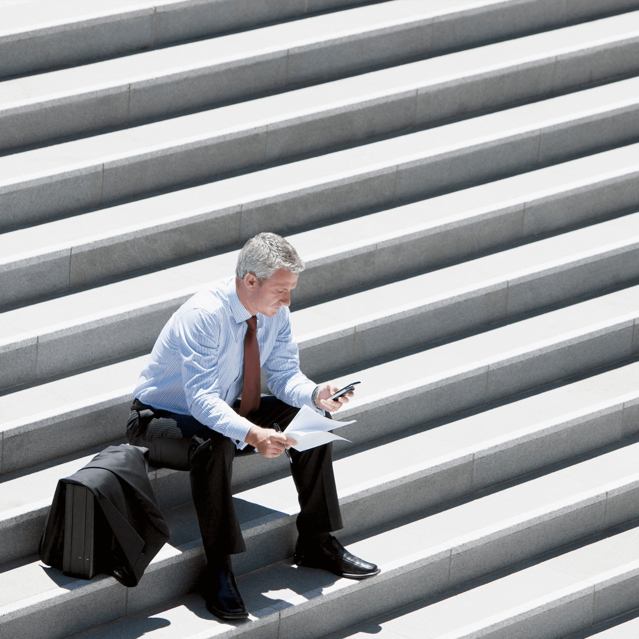 Businessman holding mobile phone and sitting on angled steps