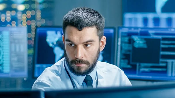Man surrounded by computer screens