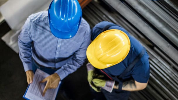 Aerial view of two workers in hardhats reviewing report