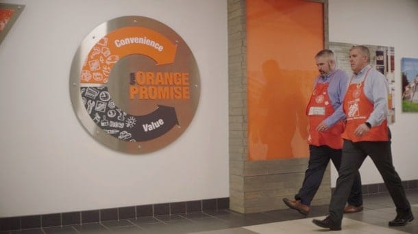 Two Home Depot workers walk down a hall