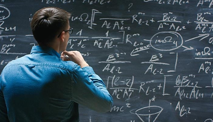 Man solving complex equations on a chalk board