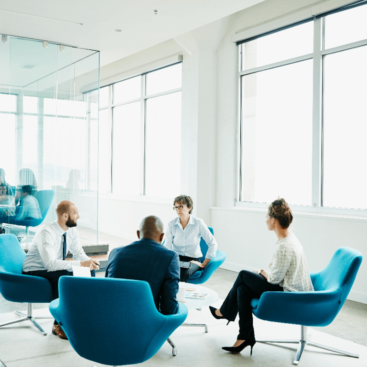 Four workers sitting down in a meeting room talking