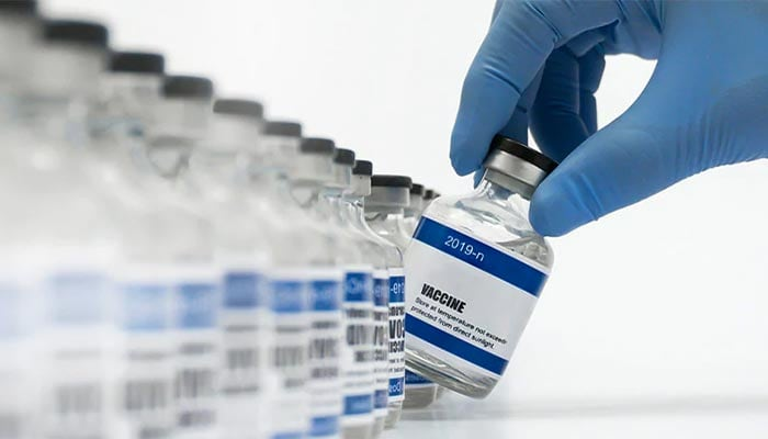A gloved hand lifts one bottle of vaccine from a row of identical bottles