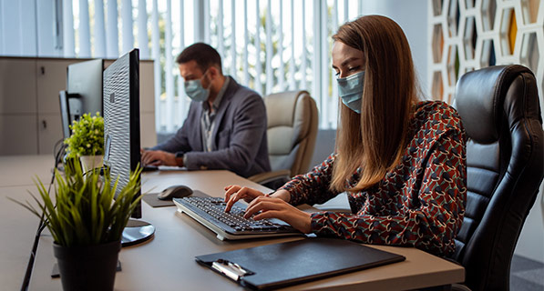 Mask-wearing business employees sitting at office desk