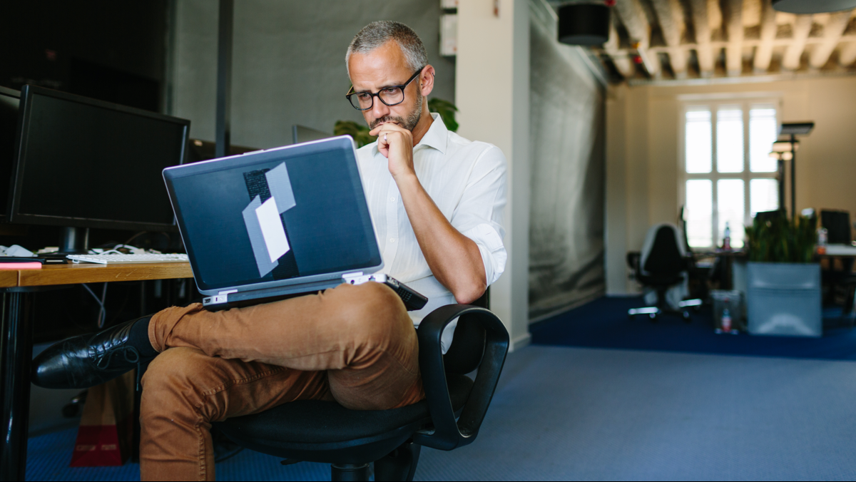 A casually dressed man with a laptop in his lap in an open-office setting