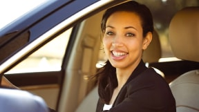 Smiling person in driver's seat of a car