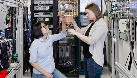 Two women working on a quantum computer part