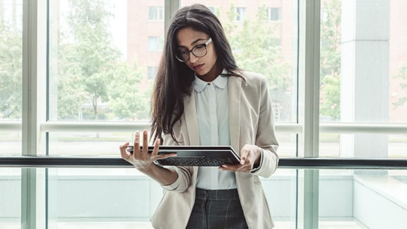 A person in a sunny office looks down at tablet computer