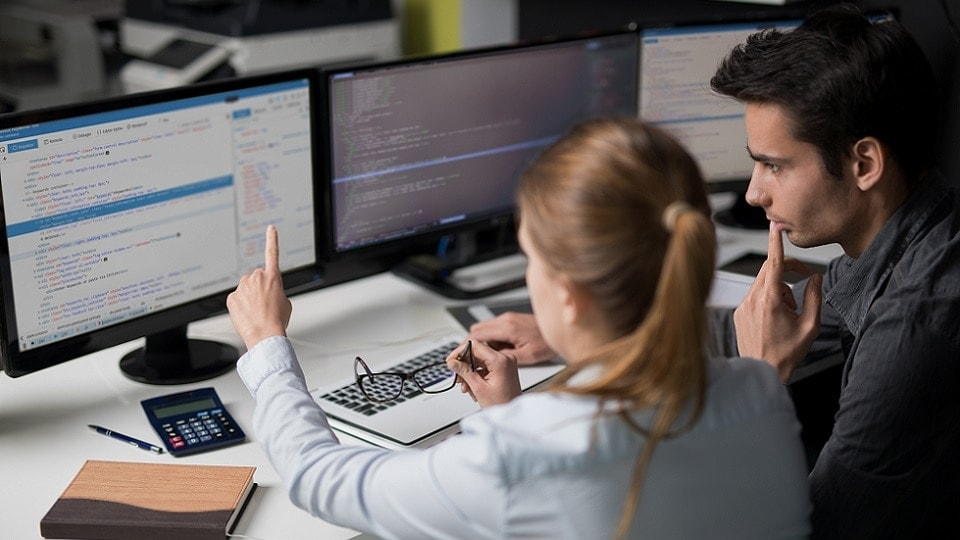 Two persons seeing web code in a screen in a work environment