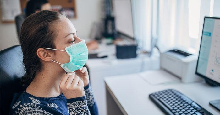 A woman wearing a mask works at her office computer