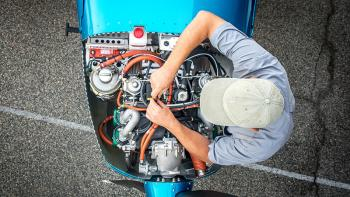 man working on small plane engine