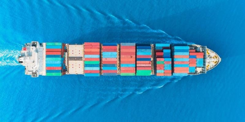 Overhead shot of a container ship sailing in blue water.