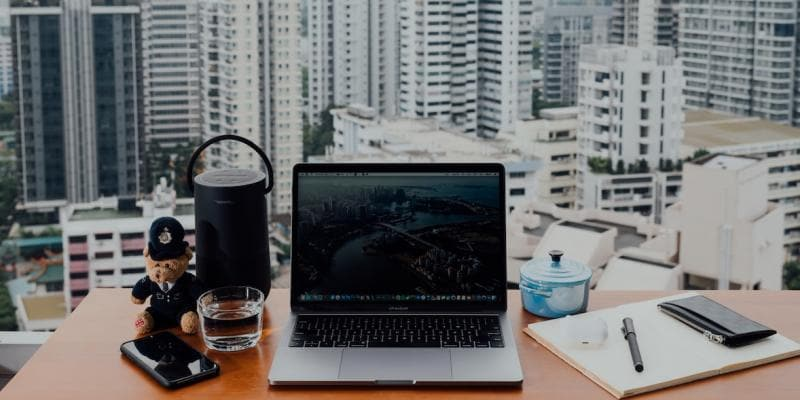 Open laptop on a counter looking out a window onto a city.