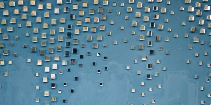 Small pieces of glass mounted on a blue wall.