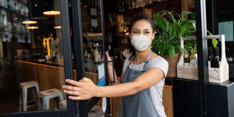 Woman with mask on at the entrance of a store