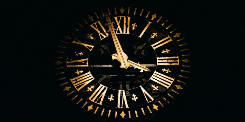 Ornate gold clock against a black background