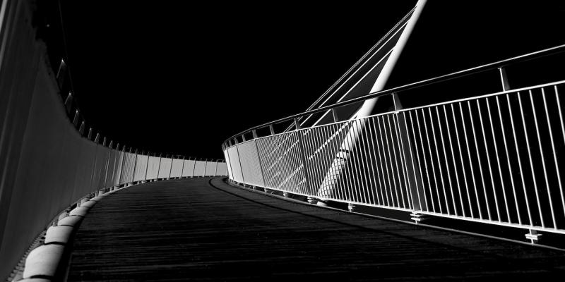 Black and white image of a curving bridge