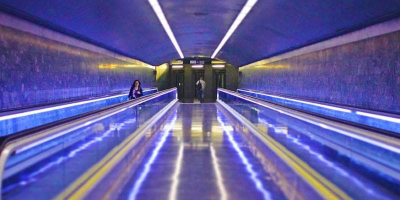 Two escalators in neon lighting
