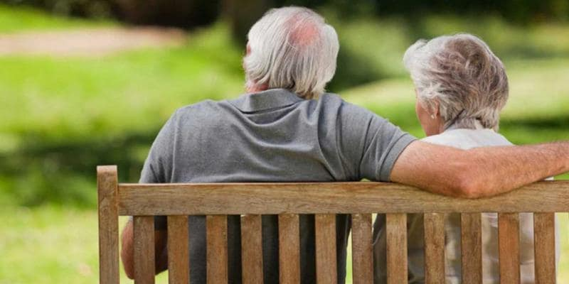Old man and woman sitting on a bench