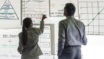 Two people working with charts on a whiteboard