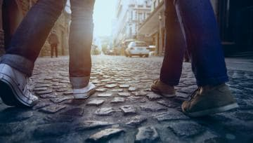 Two people walking side by side on a cobblestone street