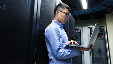 Man in data center working on laptop