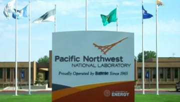 Pacific Northwest National Laboratory entrance sign with flags behind