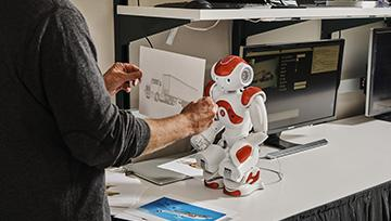 man working at desk with robot model on it