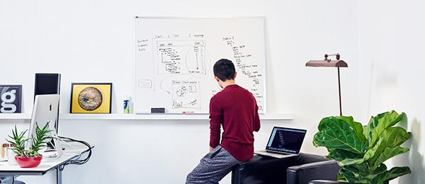A young man in a minimalist, white-walled office sitting in front of a whiteboard searching for insights on an analytics platform