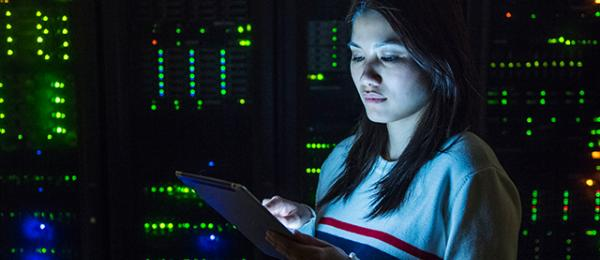 a woman using her tablet in a dark server room