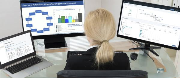 woman at desk with three monitors