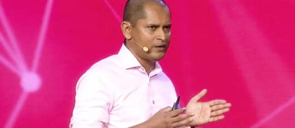 Dinesh Nirmal against a pink background