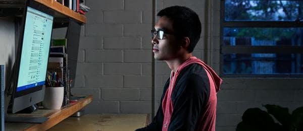 Young man looking at computer monitor