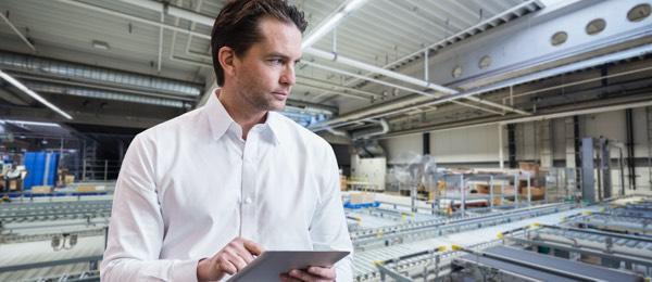 man holding tablet device in factory setting