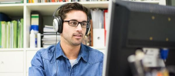 man with headphones looking at monitor