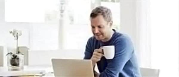 Man looking at laptop, holding coffee
