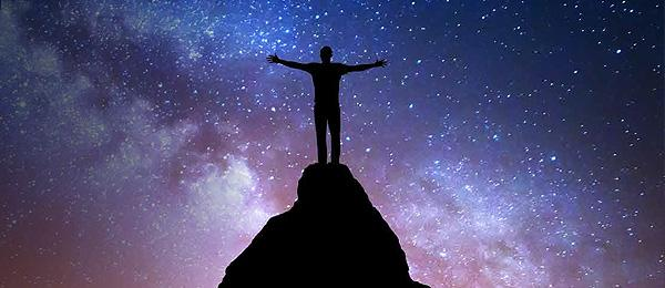 Man standing on rock with arms open at night sky