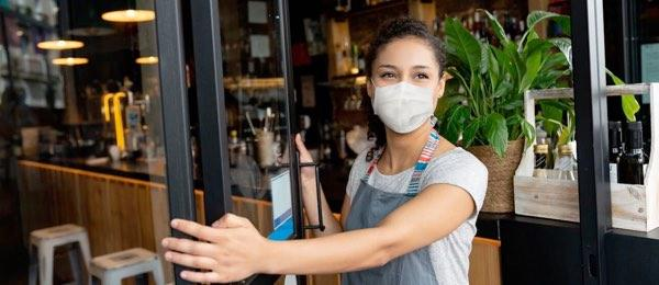 person wearing a face mask, opening restaurant door