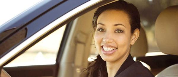 A smiling person in the driver's seat of a car