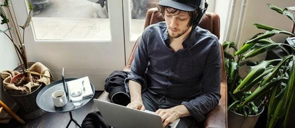 Man with headphones staring at laptop screen