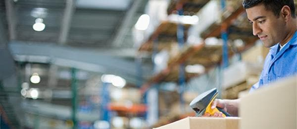 Worker in warehouse using barcode scanner on package