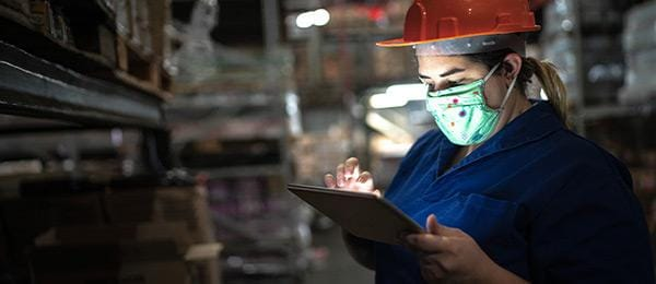 Person wearing hard hat and mask using tablet in warehouse