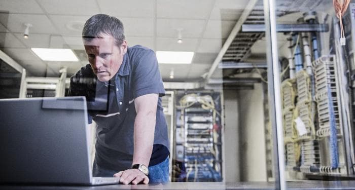 Homme dans un data center regardant l'ordinateur portable