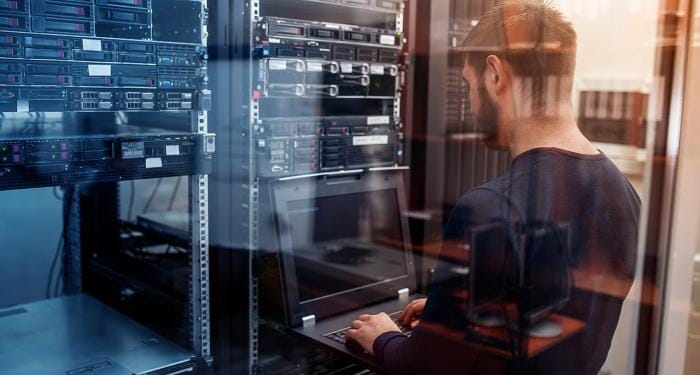 Image of a man working on a laptop in a data center